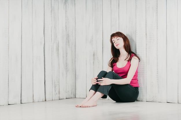Une jolie fille dans un haut rose, assise sur le sol en détente, les yeux fermés