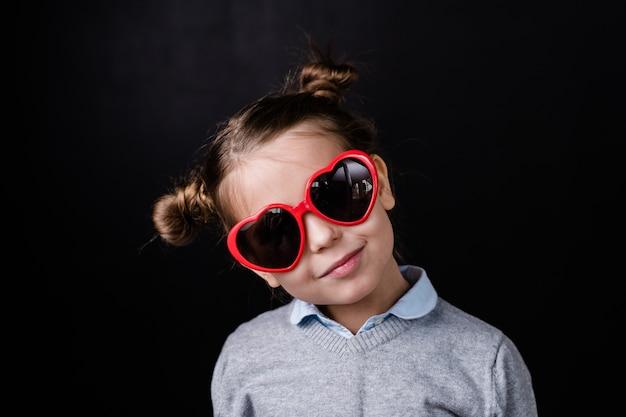 Jolie fille dans des lunettes de soleil élégantes avec lentille en forme de coeur debout devant la caméra dans l'isolement contre l'espace noir
