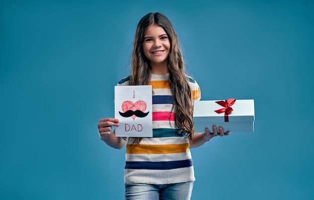 Jolie fille dans un pull multicolore rayé détient une boîte-cadeau et une carte pour son père isolé sur un bleu.