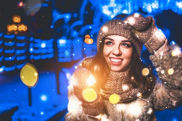 Jolie fille dans la rue avec des lumières de noël autour