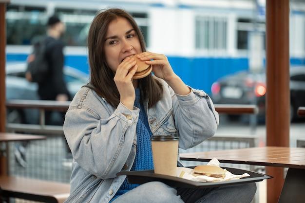 Jolie fille dans un style décontracté mange un hamburger avec du café assis sur la terrasse d'été