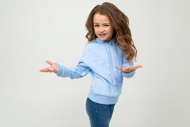 Jolie fille dans un sweat à capuche bleu indigné agitant les mains sur un mur gris clair