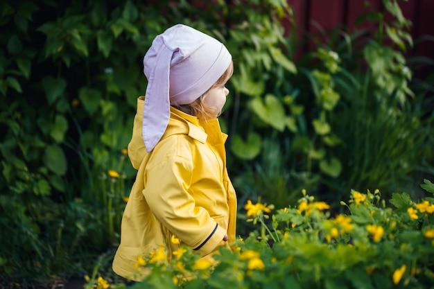 Jolie fille dans une veste jaune recueille des fleurs dans un pré. un enfant se tenait dans l'herbe verte fraîche parmi les fleurs printanières. un petit enfant fait un bouquet des premières fleurs jaunes sauvages