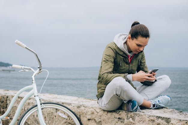 Jolie fille dans une veste verte bénéficie d'un téléphone mobile