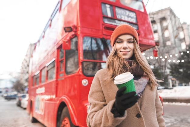 Jolie fille dans des vêtements chauds de printemps, debout avec une tasse de café en papier dans les mains d'un bus touristique rouge, regardant la caméra et souriant