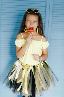 Jolie fille dans des vêtements de style hawaïen avec une sucette à la main