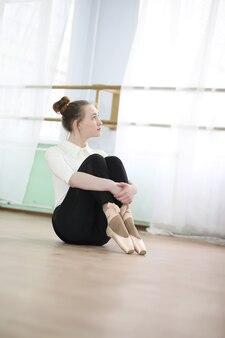 Jolie fille danseuse de ballet pratiquant à l'intérieur