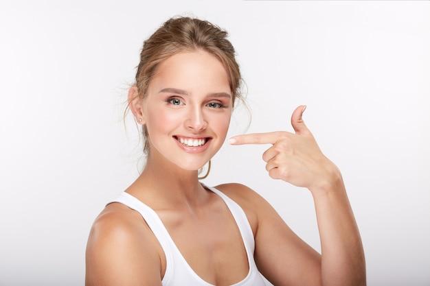 Jolie fille avec des dents blanches comme neige sur fond de studio blanc, concept de dentisterie, sourire parfait, pointant sur son sourire, portrait.