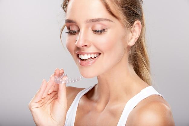 Jolie fille avec des dents blanches comme neige sur fond de studio blanc, concept de dentisterie, sourire parfait, regardant la caméra, gros plan, tenant le dentifrice, traitement des dents.