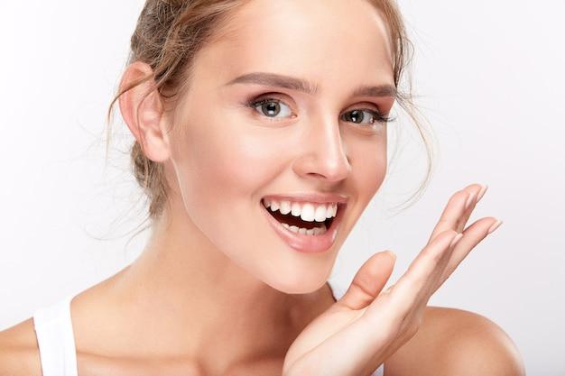 Jolie fille avec des dents blanches comme neige sur fond de studio blanc, concept de dentisterie, sourire parfait, regardant la caméra, heureux.
