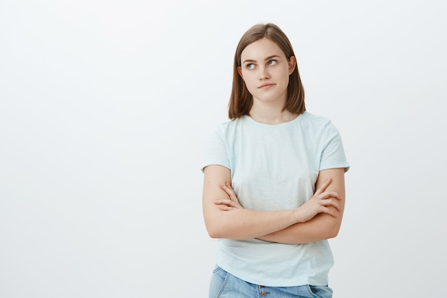 Jolie fille dérangée par un mec collant impopulaire essayant de lui demander de sortir à la gauche, irritée et ennuyée, se croisant les mains sur la poitrine et se pinçant les lèvres étant indifférent et indifférent posant sur un mur blanc