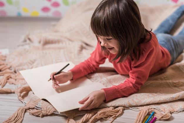Jolie fille dessinant sur papier au sol