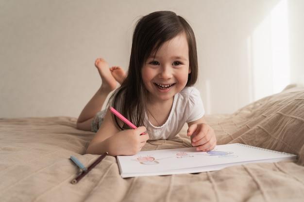 Jolie fille dessine un dessin au crayon. un enfant apprend à dessiner des gens. l'enfant est allongé sur le lit et dessine avec un crayon