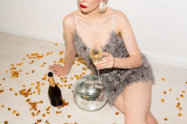 Jolie fille détendue en robe glamour tenant une flûte de champagne assis sur le sol avec des confettis dorés, une bouteille et une discoball