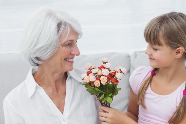 Jolie fille donnant un bouquet de fleurs à sa grand-mère