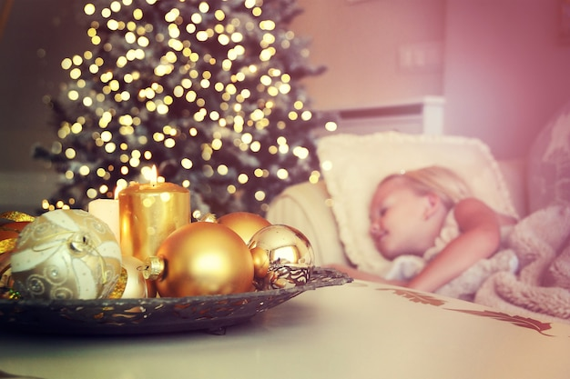 Jolie fille dormant sur le sol sous l'arbre de noël