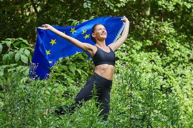 Jolie fille avec le drapeau de l'ue posant dans le parc forestier