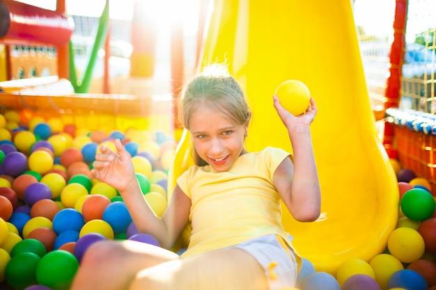 Une jolie fille drôle est assise dans une aire de jeux avec un équipement doux et lumineux et lance des balles colorées vers la caméra