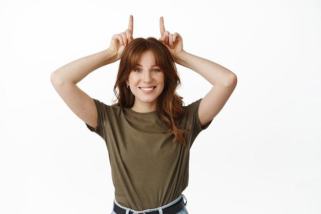 Jolie fille drôle montrant le geste des cornes de taureau et souriant les dents blanches, caractère têtu et déterminé, debout sur blanc
