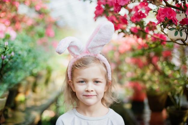 Jolie fille drôle avec des oreilles de lapin de pâques au jardin. concept de pâques. enfant riant à la chasse aux œufs de pâques