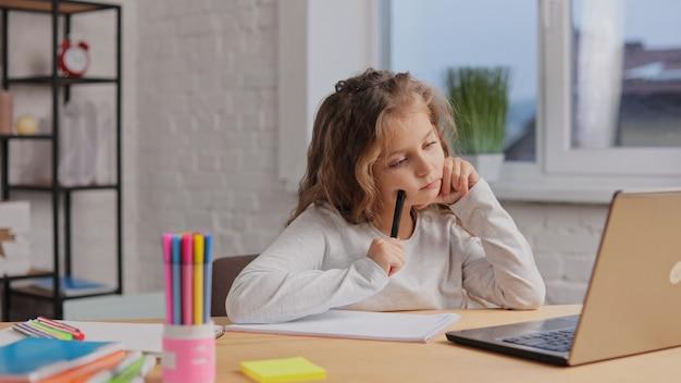 Jolie fille de l'école primaire étudie à la maison à l'aide d'un ordinateur portable. une écolière a une leçon en ligne. enseignement à distance, enseignement à domicile