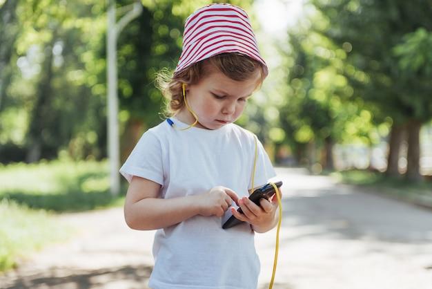 Jolie fille écoutant de la musique avec des écouteurs à l'extérieur
