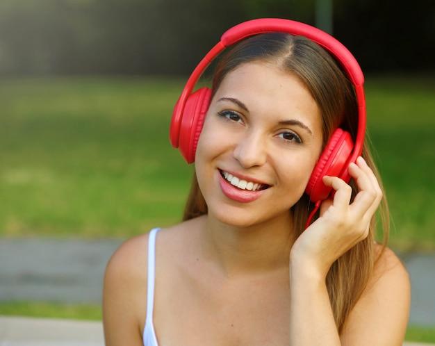 Jolie fille écoutant de la musique avec ses écouteurs dans le parc et regardant la caméra.