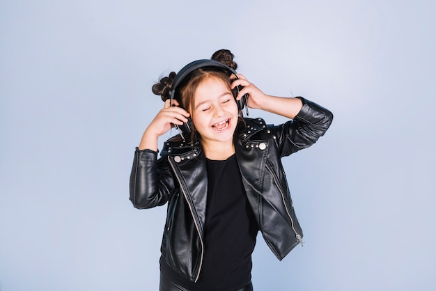 Jolie fille écoute de la musique sur le casque debout contre la toile de fond bleue
