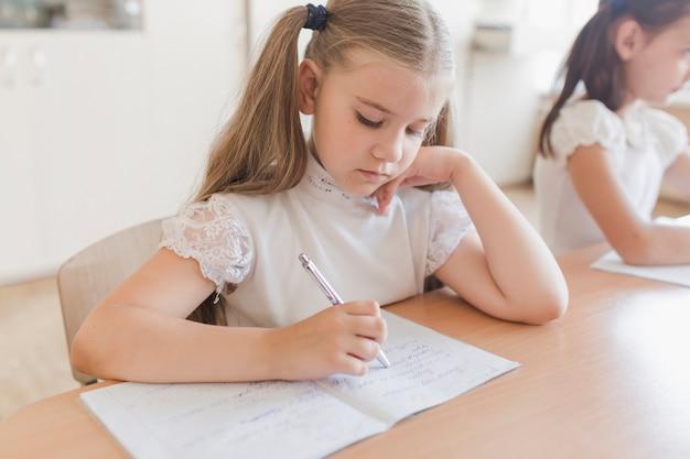 Jolie fille écrivant dans le cahier