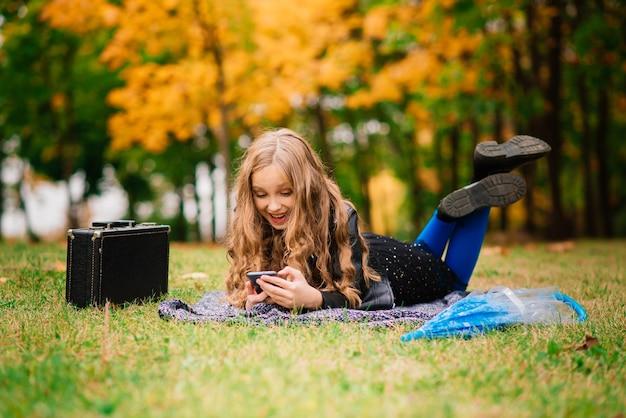 Jolie fille élégante aux longs cheveux blonds dans le parc en automne. mode pour enfants d'automne, portrait de style de vie.