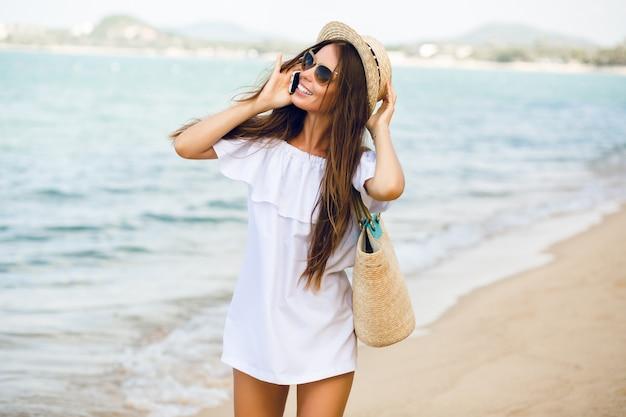 Jolie fille élégante debout sur une plage, parler sur un smartphone.