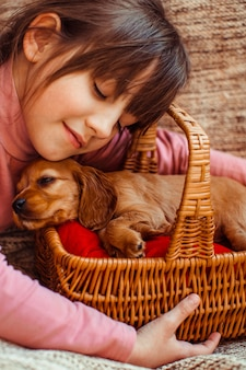 La jolie fille embarcant un panier avec un chien