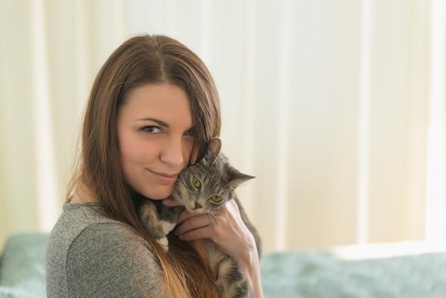 Jolie fille embrasse le petit chat gris dans la chambre le matin. thème des animaux domestiques.