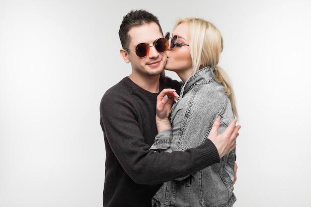 Jolie fille embrasse son homme bien-aimé qui la serre dans ses bras sur un mur gris clair