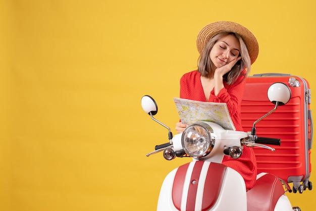 Jolie fille endormie sur un cyclomoteur avec une valise rouge tenant une carte