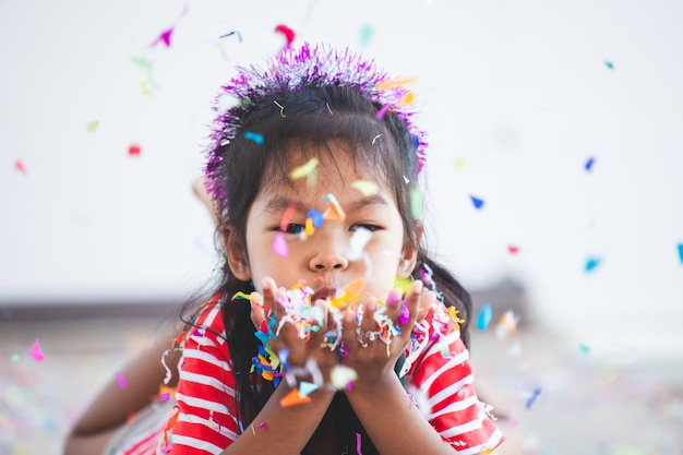 Jolie fille enfant asiatique avec des confettis colorés pour célébrer dans sa fête