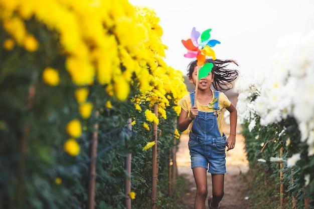 Jolie fille enfant asiatique court et joue avec un jouet d'éolienne avec plaisir dans le champ de fleurs