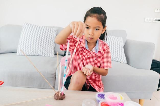 Jolie fille enfant asiatique jouant et créant avec de la pâte à modeler et des pailles. enfant concentré avec de la pâte à modeler construisant un modèle de molécule. kid et artisanat avec des choses de recyclage.