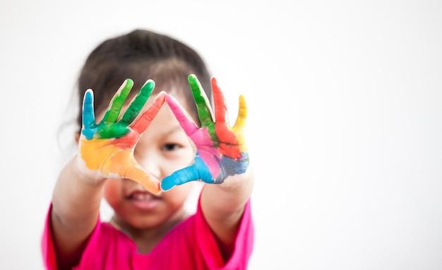 Jolie fille enfant asiatique avec des mains peintes en peinture colorée sur fond blanc