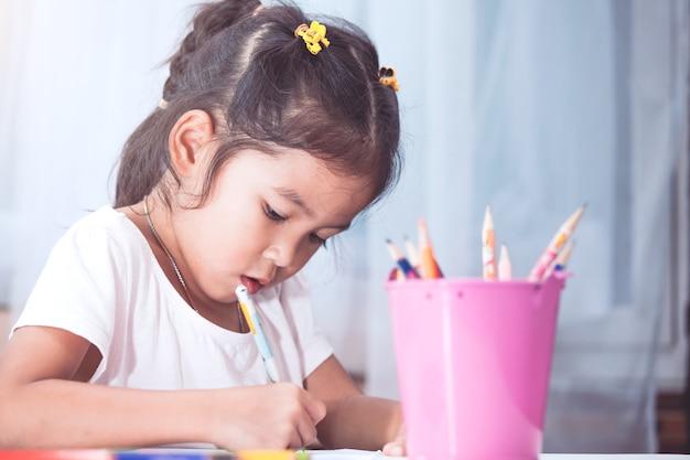 Jolie fille enfant asiatique s'amuser à dessiner et peindre avec un crayon dans le ton de couleur vintage