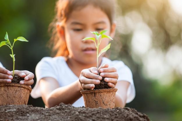 Jolie fille enfant asiatique tenant un jeune arbre pour la plantation dans des pots de fibres recyclées dans le jardin avec plaisir