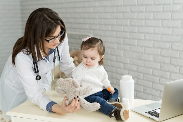 Jolie fille enfant jouant au docteur avec peluche