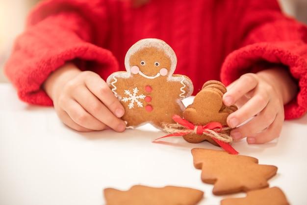 Jolie fille enfant prépare des hommes en pain d'épice pour les vacances de noël