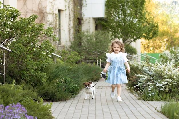 Jolie fille enfant en robe prenant un petit chien pour une promenade en plein air dans la nature. amitié entre l'animal de compagnie et les enfants.
