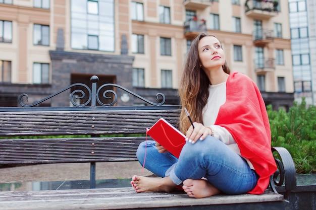 Une jolie fille est assise sur un banc.