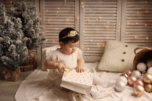 Une jolie fille est assise sur une couverture tricotée et joue avec un paquet de cadeaux pour la nouvelle année