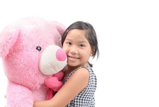 Jolie fille étreignant nounours rose isolé