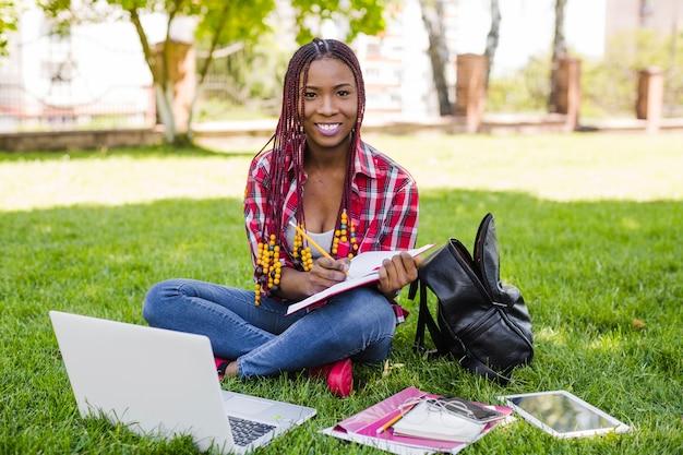 Jolie fille avec des études posant dans le parc