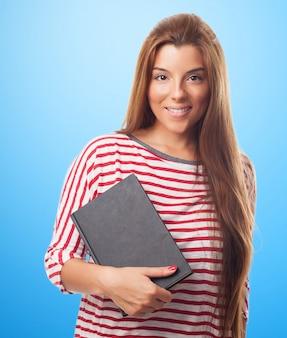Jolie fille étudiante posant avec bloc-notes
