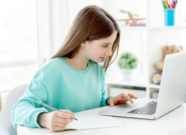 Jolie fille étudie avec un ordinateur portable, l'éducation en ligne